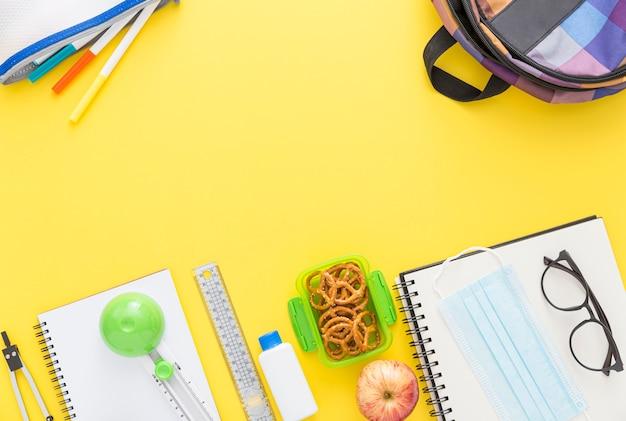 Draufsicht auf schulmaterial mit notizbuch und brille