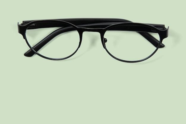 Draufsicht auf schwarze brille auf hellgrünem hintergrund