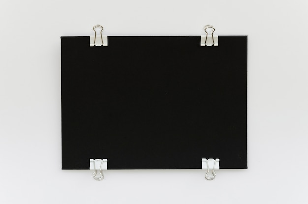 Draufsicht auf schwarzes papier mit metallklammern an den seiten