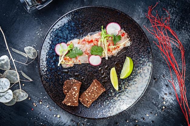 Draufsicht auf seebarsch-ceviche diente in der dunklen platte auf schwarzem steinhintergrund. draufsicht essen. flache meeresfrüchte. frische und leckere cebiche. roher fisch. lateinamerikanische küche. mittagessen