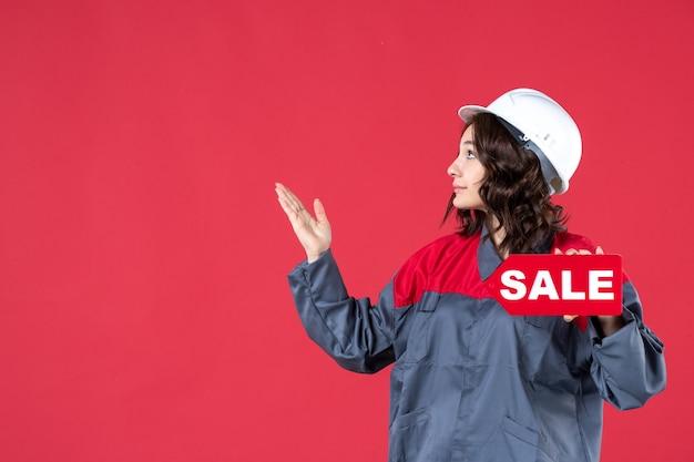 Draufsicht auf selbstbewusst lächelnde baumeisterin in uniform, die einen schutzhelm trägt und das verkaufssymbol zeigt, das auf der rechten seite auf isoliertem rotem hintergrund nach oben zeigt