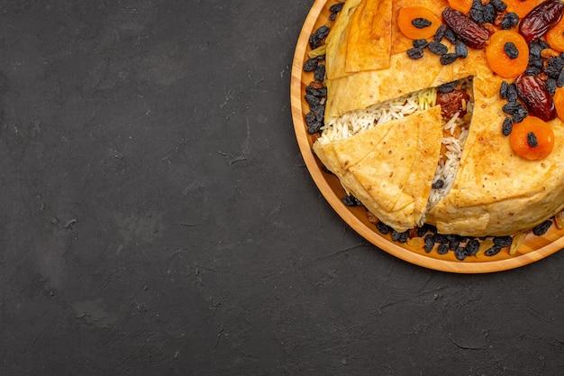 Draufsicht auf shakh plov köstliches reismehl, das innerhalb des runden teigs mit rosinen auf der grauen oberfläche gekocht wird