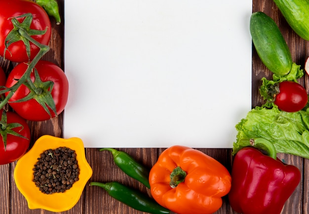 Draufsicht auf skizzenbuch und frisches gemüse bunte paprika grüne chilischoten tomaten und schwarze pfefferkörner auf rustikalem holztisch