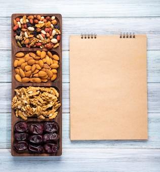 Draufsicht auf skizzenbuch und nüsse mischen mit walnussmandel und süßen getrockneten dattelfrüchten auf holz