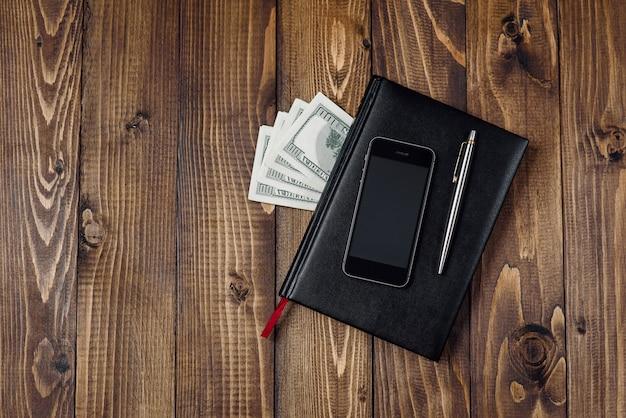 Draufsicht auf smartphone, uhr, stift, notizbuch und geld