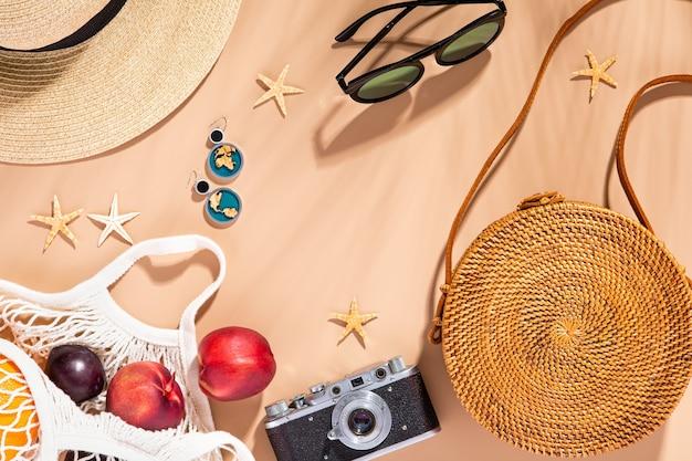 Draufsicht auf sommeraccessoires auf naturtonhintergrund mit palmblattschatten, flache lage