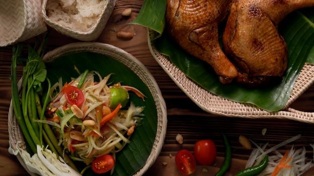 Draufsicht auf somtum, traditionelles thailändisches essen mit gegrilltem huhn und klebrigem reis