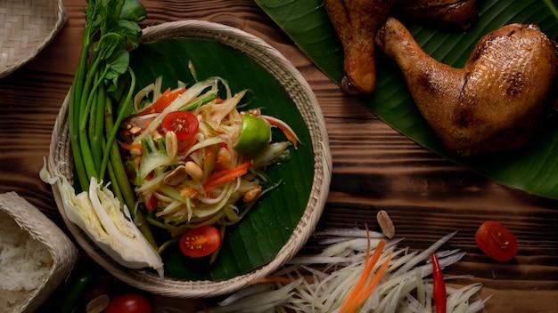 Draufsicht auf somtum, traditionelles thailändisches essen mit gegrilltem huhn, zutaten und klebreis