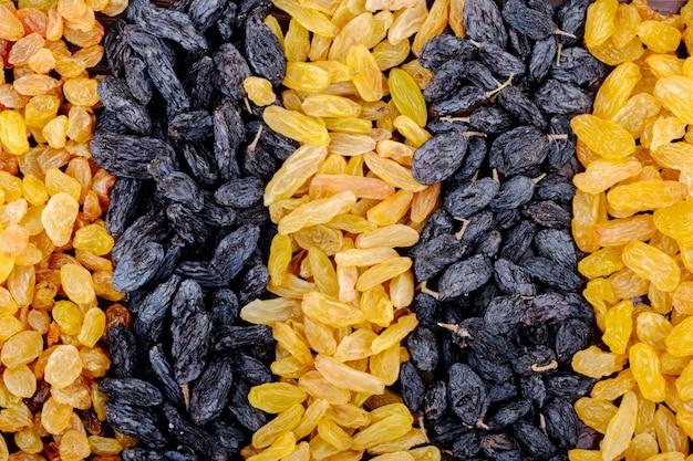 Draufsicht auf sortiment von getrockneten früchten schwarzen und gelben rosinen
