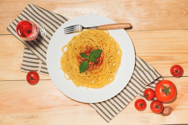 Draufsicht auf spaghetti mit tomatensauce und fleisch auf holztisch.