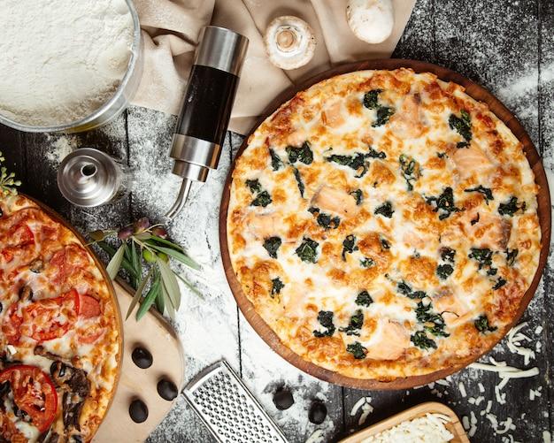 Draufsicht auf spinatpizza und die hälfte der mischpizza