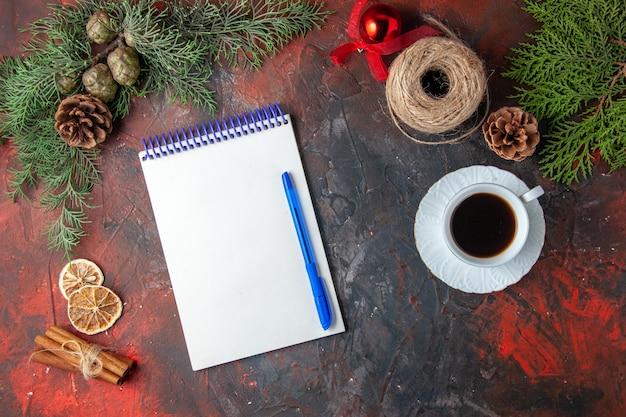 Draufsicht auf spiralnotizbücher mit stift-tannenzweig-zimt-limonen-koniferenkegel und einer tasse schwarzem tee auf dunklem hintergrund