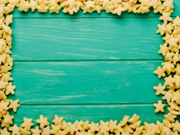 Draufsicht auf sternförmige cornflakes, die als rahmen mit kopienraum auf grünem hölzernem hintergrund angeordnet sind