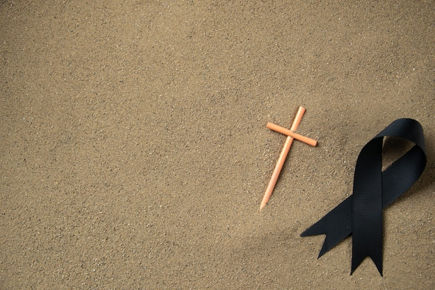 Draufsicht auf stockkreuz mit schwarzer schleife auf dem sand