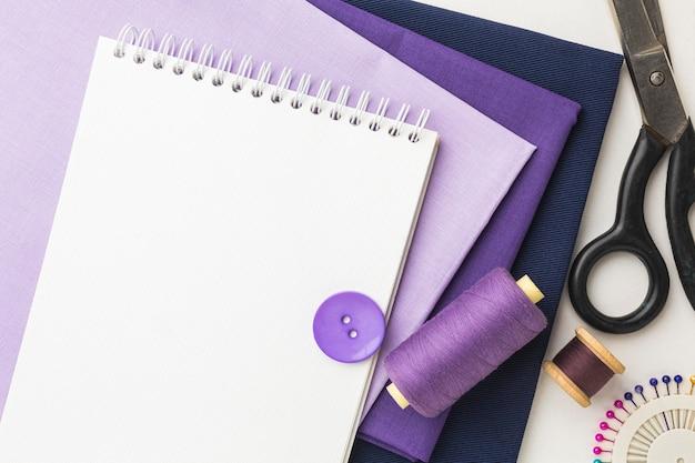 Draufsicht auf stoffe mit notizbuch und faden