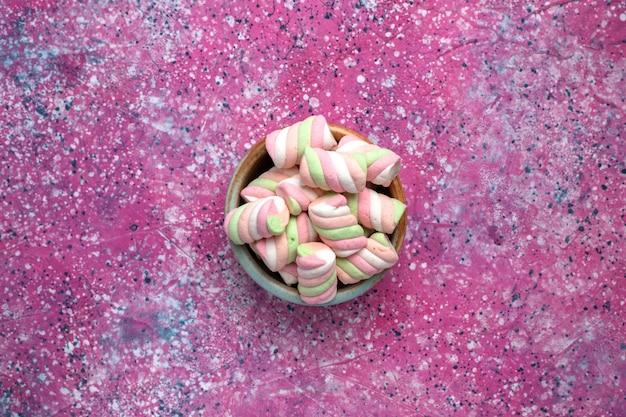 Draufsicht auf süß gefärbte marshmallows, die innerhalb des runden topfes auf der rosa oberfläche wenig gebildet werden