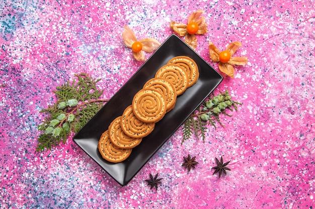 Draufsicht auf süße kekse in schwarzer form mit physalisierungen auf hellrosa oberfläche