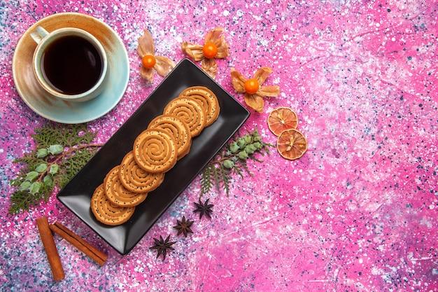 Draufsicht auf süße kekse in schwarzer form mit zimt und tee auf hellrosa oberfläche