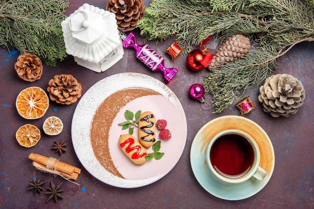 Draufsicht auf süße kekse mit tasse tee auf schwarz on