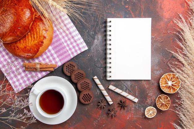 Draufsicht auf süße kuchen mit tee- und keksröllchen