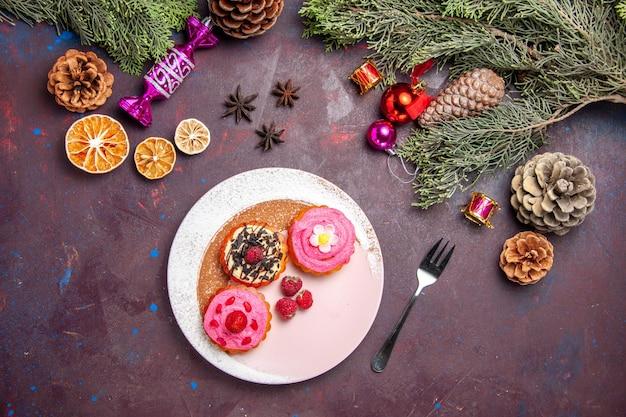 Draufsicht auf süße leckere kuchen mit sahne und früchten auf schwarz