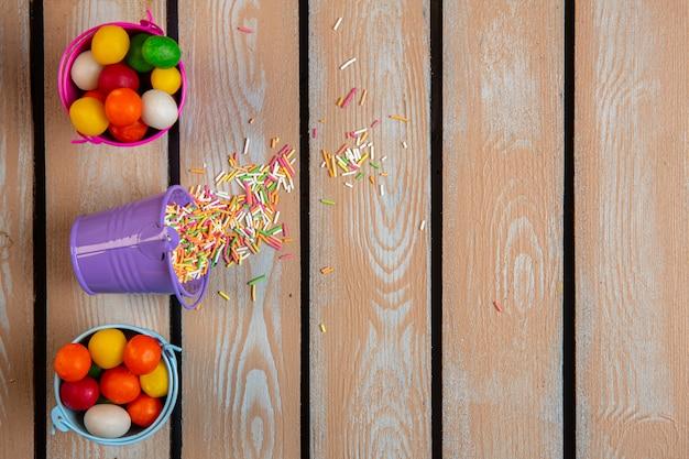 Draufsicht auf süßigkeiten und bunte streusel, die vom kleinen eimer verstreut werden