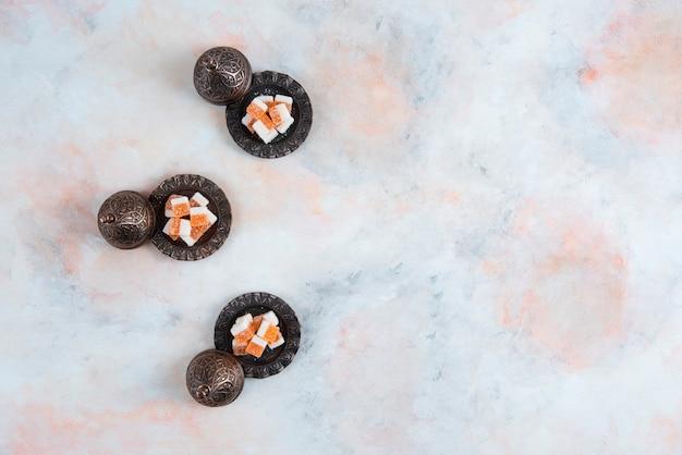 Draufsicht auf süßigkeitengeschirr und orangefarbene bonbons