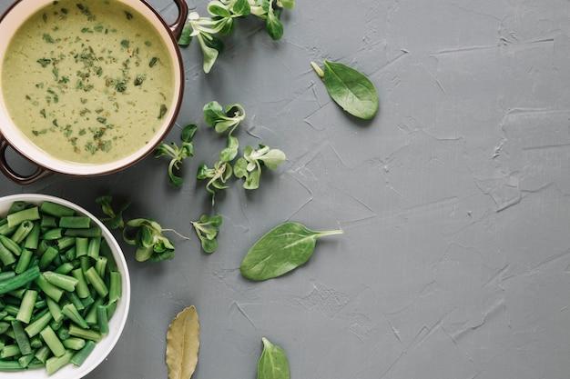 Draufsicht auf suppe und grüne bohnen mit kopienraum