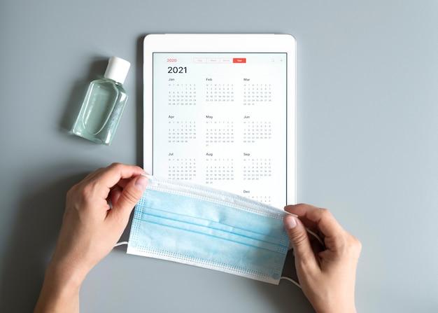 Draufsicht auf tablette mit offenem kalender für 2021 jahre und schützender medizinischer maske und händedesinfektionsmittel in den händen der frau auf grau