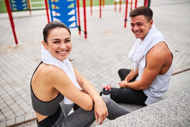 Draufsicht auf taillenhöhe porträt einer lächelnden frau mit handtuch, die nach dem gemeinsamen training im freien in der nähe ihres freundes sitzt