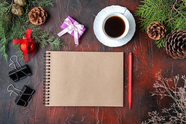 Draufsicht auf tannenzweige, eine tasse schwarztee-dekorationszubehör und geschenk neben notizbuch mit stift auf dunklem hintergrund