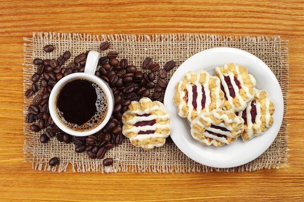 Draufsicht auf tasse kaffee und kekse auf holztisch