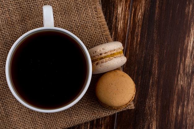 Draufsicht auf tasse tee und kekssandwiches auf sackleinen und hölzernem hintergrund mit kopienraum