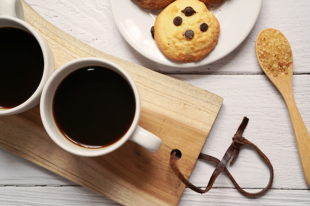 Draufsicht auf tassen heißen kaffees mit einem löffel zucker und schokoladenkeks auf holzteller