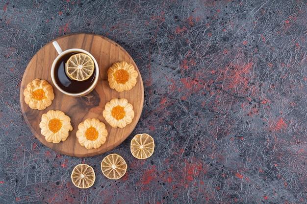 Draufsicht auf tee und hausgemachte kekse auf holzbrett.