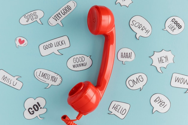 Draufsicht auf telefonhörer mit chatblasen