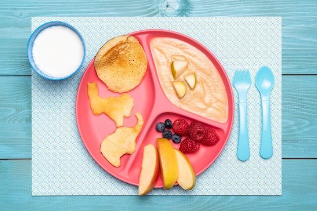 Draufsicht auf teller mit babynahrung und sortiment von früchten