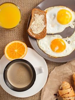 Draufsicht auf teller mit spiegeleiern und toast mit butter, glas orangensaft, tasse schwarzen kaffee, croissants auf sackleinen. ansicht von oben.