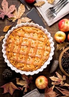 Draufsicht auf thanksgiving-apfelkuchen mit herbstlaub und tannenzapfen
