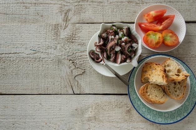 Draufsicht auf tintenfischsalat mit scheiben geröstetem baguette und tomaten auf rustikalem holzhintergrund. typisches mediterranes vorspeisenessen