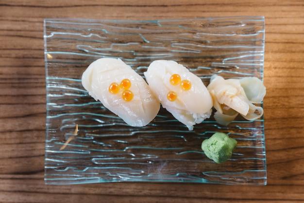 Draufsicht auf tintenfischsushi-belag mit lachskaviar, serviert mit wasabi und eingelegtem ingwer.