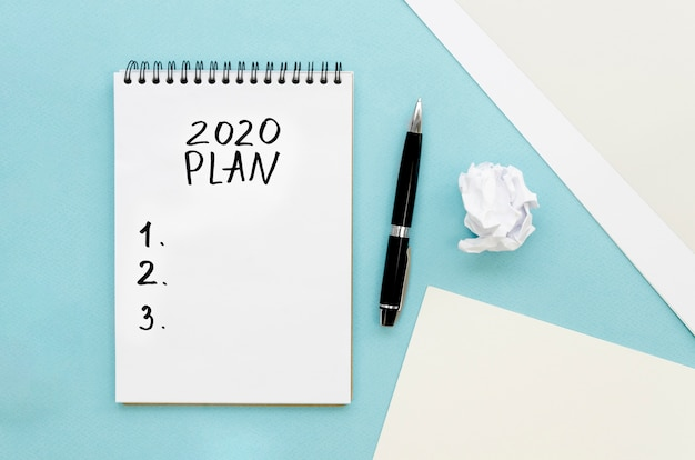 Draufsicht auf tischplatte mit plan für das neue jahr auf notizbuch