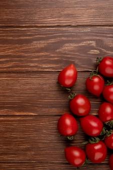 Draufsicht auf tomaten auf der rechten seite und holzoberfläche mit kopierraum