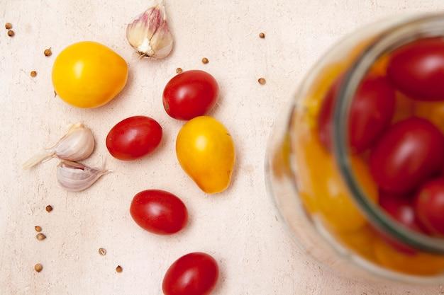 Draufsicht auf tomaten, knoblauch und gewürze zum beizen. home dosenkonzept
