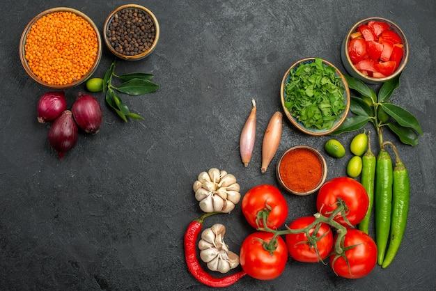 Draufsicht auf tomaten tomaten peperoni gewürze kräuter schüssel linsenzwiebel schwarzer pfeffer