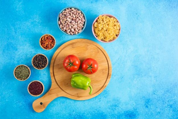 Draufsicht auf tomaten und paprika auf holzbrett vor zwei schüsseln. bohnen und nudeln mit gewürzen.