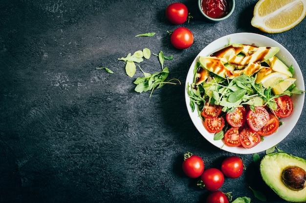 Draufsicht auf tomatensalat rucola avocado zitrone in weißer platte auf schwarzem hintergrund
