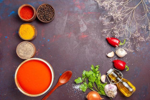 Draufsicht auf tomatensuppe gekocht aus frischen tomaten mit verschiedenen gewürzen auf schwarz