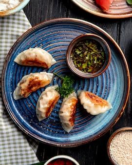 Draufsicht auf traditionelle asiatische knödel mit fleisch und gemüse, serviert mit sojasauce auf einem teller auf rustikalem tisch
