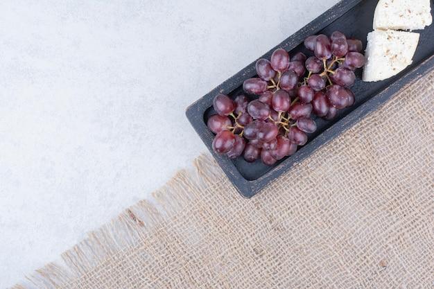 Draufsicht auf trauben mit weißkäse auf sackleinen. foto in hoher qualität